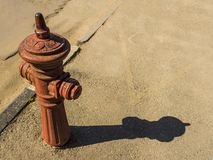 Den gamla brandposten står vid vägen som tänds av solen arkivfoto