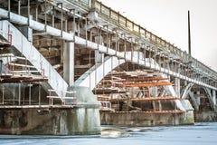 Den gamla bron över floden på service, med att hänga under den ställningen, under reparationer Arkivbild