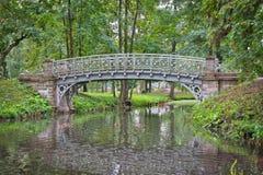 Den gamla bron över vatten i slotten parkerar i Gatchina Royaltyfri Foto