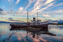 Den gamla brutna ångbåten strandade ashore i ett solnedgångljus, Ushuaia Arkivbilder