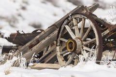 Den gamla brutna vagnen med rullar in snö arkivbild