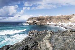 Den gamla byn Los Molinos för fiskare` s med klippor och vaggar med det blå snurra havet och himmel Fotografering för Bildbyråer