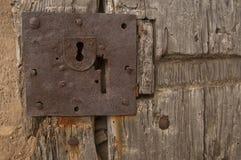 Den gamla dörren med låser och spikar arkivbild