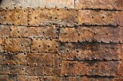 Den gamla dörren med metall lappar och spikar royaltyfri bild