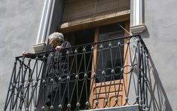 Den gamla damen hålla ögonen på från den balkongen ståtar på caballos Del Vino i Caravaca de la Cruz, Spanien på Maj 2nd 2019 royaltyfri foto