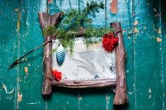 Den gamla dammiga zekraloen med poutinoy och skrapor knäcker på den röda trägolvet målade dekorerade julgranen för olje- målarfär Arkivfoton