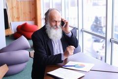 Den gamla erfarna mannen för bankrörelsekontot ger rådgivning, genom att använda ny sma Royaltyfri Bild