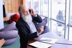 Den gamla erfarna mannen för bankrörelsekontot ger rådgivning, genom att använda ny sma Arkivbild