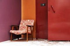Den gamla fåtöljen kasserade på ingångsdörren i lilor och burgundy c Arkivbild
