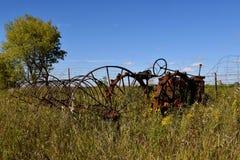 Den gamla förrådsplatsen krattar och traktoren arkivfoton
