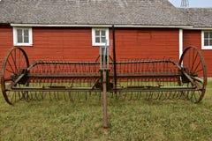 Den gamla förrådsplatsen krattar parkerat av ett rött skjul arkivbild