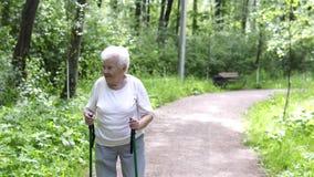 Den gamla farmodern går med pinnar för att gå på vägen arkivfilmer