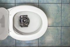 Den gamla filmkameran som tas paus i toaletten royaltyfri fotografi