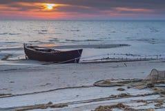 Den gamla fiskebåten på stranden av det baltiska havet på soluppgång Arkivfoton