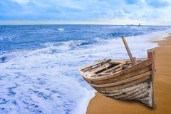 Den gamla fiskebåten strandade på en strand i solig dag Arkivbild