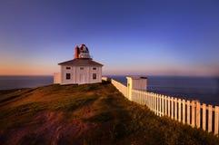 Den gamla fyren på uddespjutet, Newfoundland på solnedgången Arkivfoto