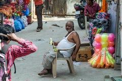 Den gamla grabben som placerar och äter bananen Arkivfoton