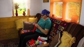 Den gamla höga farmorkvinnan sitter på soffan och sticker strumpor stock video