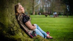 Den gamla höga kvinnan kopplar av på ett träd i en allmänhet parkerar under dag royaltyfria foton