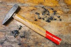 Den gamla hammaren och avslutningen spikar på en tabell i ett seminarium Arkivfoton
