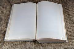 Den gamla hardcoverboken med dogearred tomma sidor som ligger på säckväv - hyra rum för kopia royaltyfri bild