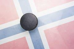Den gamla hockeypucken är på isen med den Norge flaggan Royaltyfri Fotografi