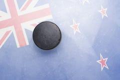 Den gamla hockeypucken är på isen med den Nya Zeeland flaggan Royaltyfri Bild