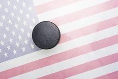 Den gamla hockeypucken är på isen med den USA flaggan Royaltyfria Foton