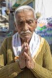 Den gamla indiska manhälsningen med hans gömma i handflatan tillsammans Royaltyfri Foto
