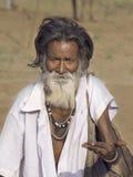 Den gamla indiska tiggaren väntar på allmosa på en gata pushkar india Arkivfoto