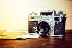Den gamla kameran är på tabellen på en bunt av foto royaltyfri fotografi