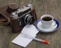Den gamla kameran, kaffet och anteckningsboken med handtaget på ett trä Arkivbilder
