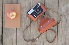 Den gamla kameran med boken på en träbakgrund royaltyfri foto