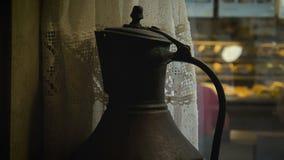 Den gamla kannan står på en fönsterbräda i en kafécloseup arkivfilmer