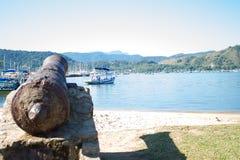 Den gamla kanonen pekas till fj?rden Flera fartyg seglar p? det bl?a vattnet royaltyfria foton