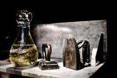 Den gamla klädjärn och vasen i antikt shoppar fönstret royaltyfri bild
