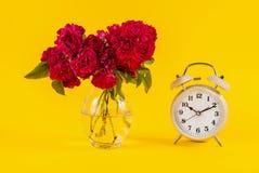 Den gamla klockan och den röda rosen blommar i vas på gul bakgrund Royaltyfria Foton