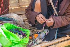 Den gamla kullestamkvinnan gör ett hemslöjdarmband Arkivbild