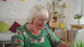 Den gamla kvinnan använder en bärbar dator, medan sitta i vardagsrumslutet upp lager videofilmer
