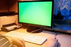 Den gamla kvinnan arbetar på datoren hemma, med den gröna skärmen, din tex arkivbilder