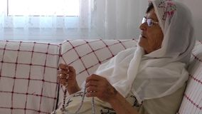 Den gamla kvinnan ber med radbandet