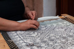 Den gamla kvinnan broderar en vit snör åt Royaltyfri Fotografi