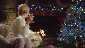 Den gamla kvinnan dricker vin vid julgranen arkivfilmer