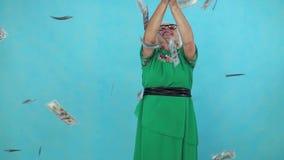 Den gamla kvinnan fångar att flyga pappers- sedlar på blå bakgrund långsam mo lager videofilmer