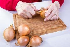 Den gamla kvinnan förbereder lökar Royaltyfri Foto