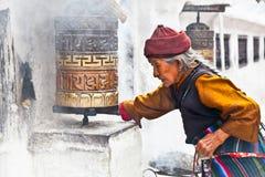 Den gamla kvinnan går runt om bönekvarnar i Bouddanathen Stupa, Kat Royaltyfria Foton