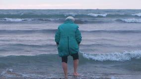 Den gamla kvinnan i hatt och omslag går barfota i havsvatten i vinter på solnedgången tillbaka sikt stock video