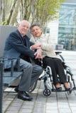 Den gamla kvinnan i rullstol med frusammanträde parkerar in Arkivfoton