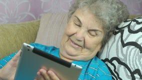 Den gamla kvinnan kopplar av genom att använda en minnestavladator lager videofilmer