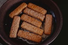 Den gamla kvinnan lagar mat fiskpinnar i panna royaltyfri bild